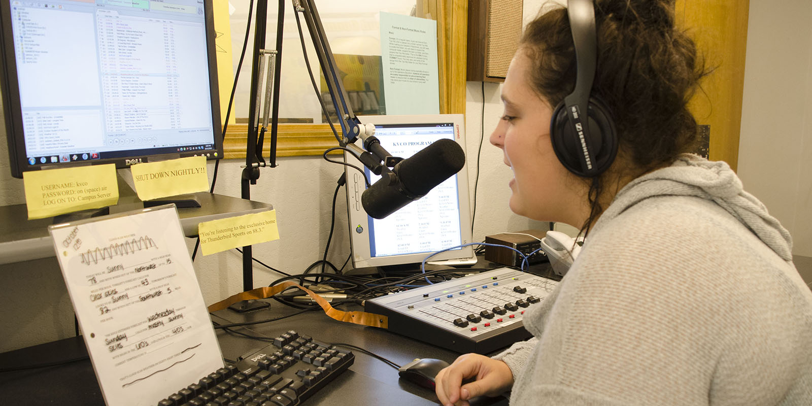 A student DJ reading a script for the radio station.