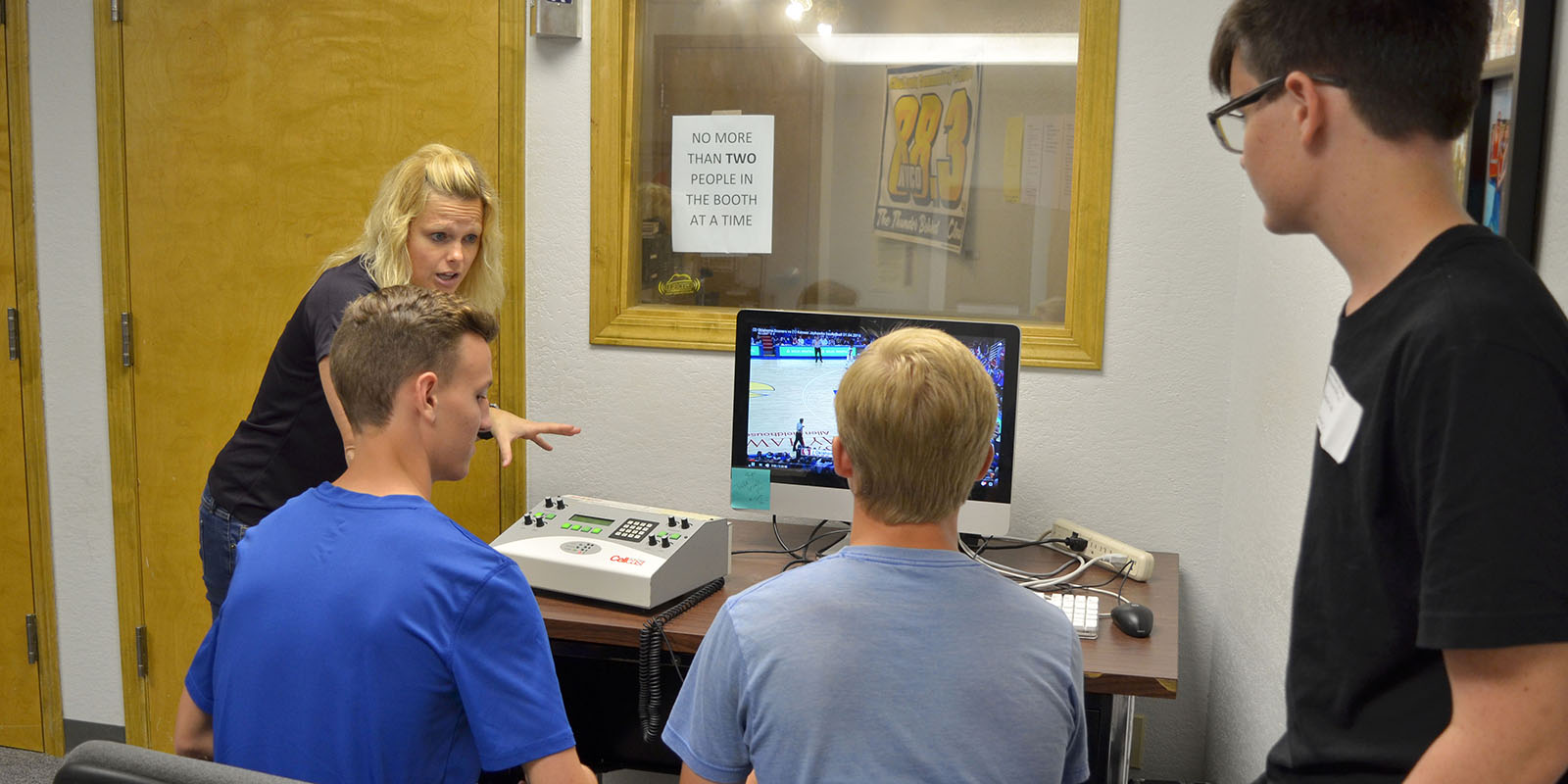 An instructor teaching students how to do play by play on the radio.