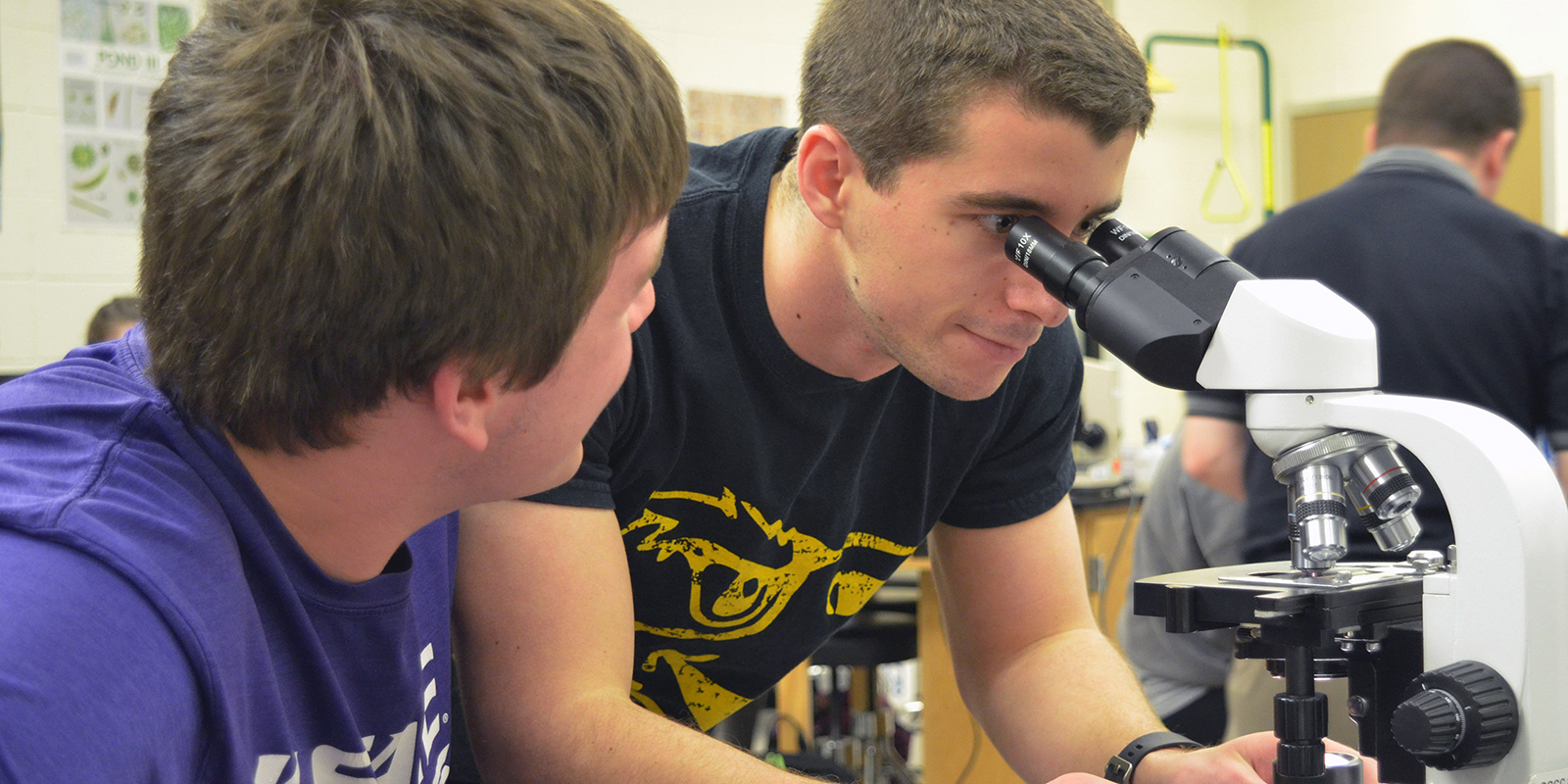 Two students looking at a microscope.