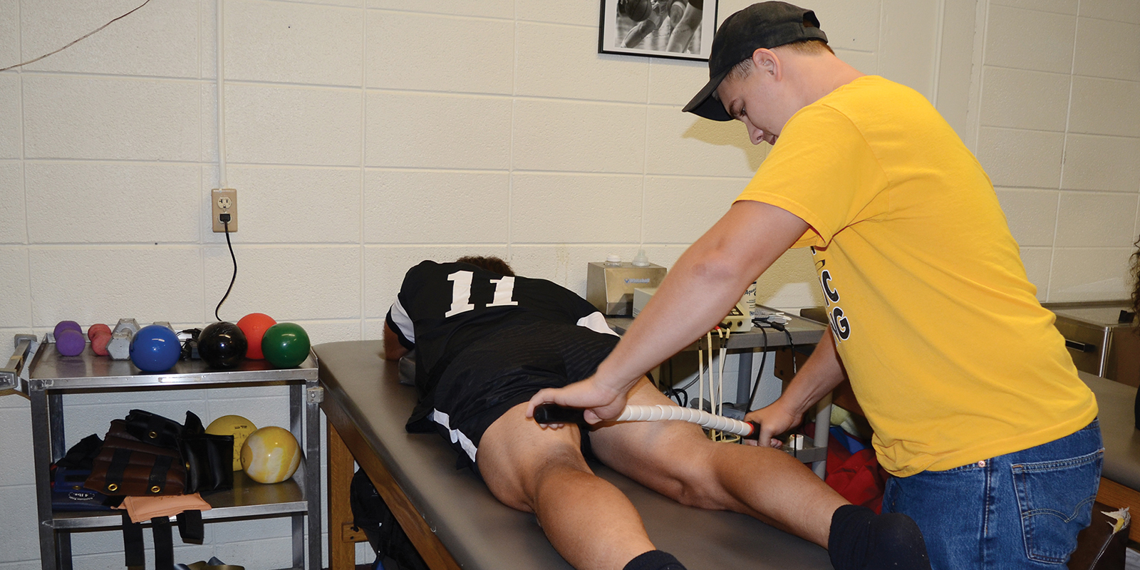 A student athletic trainer treating an athlete.